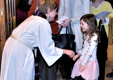 Pastor Tiffany Sundeen greeting a child at Olivet Lutheran Church
